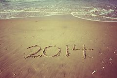 O ano novo 2014 é conceito de vinda escrito na areia da praia. efeito do vintage Imagem de Stock