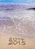 O ano novo 2015 é conceito de vinda - a inscrição 2014 e 2015 em uma areia da praia, a onda está cobrindo 2014 Fotos de Stock Royalty Free