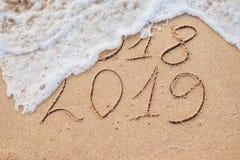 O ano novo 2019 é conceito de vinda - a inscrição 2018 e 2019 em uma areia da praia, a onda está cobrindo quase os dígitos 2018 imagens de stock royalty free