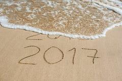 O ano novo 2017 é conceito de vinda - a inscrição 2016 e 2017 em uma areia da praia, a onda está cobrindo quase os dígitos 2016 Fotografia de Stock Royalty Free