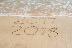 O ano novo 2018 é conceito de vinda - a inscrição 2017 e 2018 em uma areia da praia, a onda está cobrindo quase os dígitos 2017 fotografia de stock