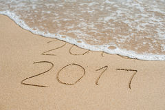 O ano novo 2017 é conceito de vinda - a inscrição 2016 e 2017 em uma areia da praia, a onda está cobrindo quase os dígitos 2016 Foto de Stock
