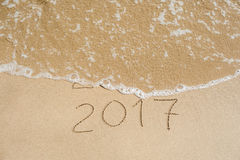 O ano novo 2017 é conceito de vinda - a inscrição 2016 e 2017 em uma areia da praia, a onda está cobrindo quase os dígitos 2016 Imagem de Stock