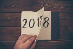 O ano novo 2018 é conceito de vinda A mão lança a folha do bloco de notas na tabela de madeira 2017 estão girando, 2018 estão abr Foto de Stock Royalty Free