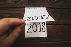 O ano novo 2018 é conceito de vinda A mão lança a folha do bloco de notas na tabela de madeira 2017 estão girando, 2018 estão abr Foto de Stock