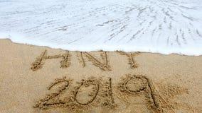 O ano novo, 2019 escreve na praia da areia e na vista para o mar, 2019 na praia fotografia de stock royalty free