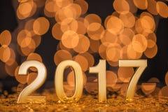 O ano novo feliz 2017 com ouro ilumina o fundo do bokeh Imagem de Stock