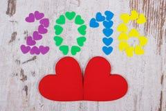 O ano novo feliz 2016 fez de corações coloridos e de corações de madeira vermelhos Imagens de Stock