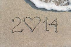 O ano novo feliz 2014 no Sandy Beach do mar com coração, ama concentrado Fotografia de Stock Royalty Free