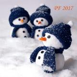 O ano novo feliz PF 2017 com três bonecos de neve - colora o branco e o azul Foto de Stock Royalty Free