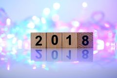 O ano novo feliz 2018, 2018 text o bloco de madeira no fundo do bokeh Foto de Stock Royalty Free