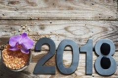 O ano novo 2018, termas ajustou-se na tabela de madeira, o coco e o sal de banho, a flor das orquídeas e as pedras para a massage imagens de stock royalty free