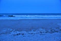O anoitecer começa a cobrir a linha costeira enquanto as ondas recuam de sua maré alta da tarde fotos de stock