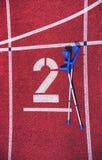 O antebraço crutches no número vermelho da pista de atletismo no estádio fotos de stock royalty free
