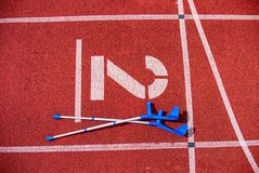 O antebraço crutches no número vermelho da pista de atletismo no estádio imagens de stock royalty free