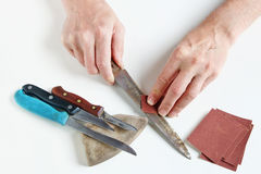 O antigo mestre tenta apontar facas de cozinha oxidadas em seu de branco Imagens de Stock