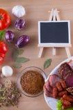 O aperitivo da carne na placa gosta do jamon, do bacon, do salame com vegetais e do espaço da cópia no quadro-negro imagem de stock