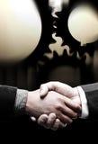O aperto de mão com preto engrena o fundo Foto de Stock Royalty Free