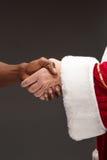 O aperto de mão da mão de Santa Claus e da mão do homem africano Fotografia de Stock Royalty Free