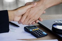 O aperto de mão da mulher de negócio dois após o trabalho junto e concorda com seu projeto no escritório com algum gráfico de pap fotografia de stock