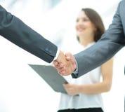 O aperto de mão de dois homens de negócios no fundo dos peritos faz Fotografia de Stock