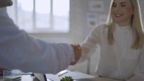 O aperto de mão de fala fêmea novo hora do candidato de trabalho ou do gerente de banco obtém contratado na entrevista, corretor  video estoque
