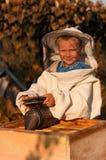 O apicultor do rapaz pequeno trabalha em um apiário na colmeia fotografia de stock
