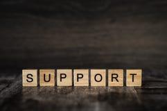 O apoio da palavra é feito de cubos de madeira brilhantes com letras pretas Imagem de Stock