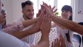 O apoio e a ajuda, os homens e a mulher sentando-se no círculo dão cinco junto na psicoterapia do grupo filme