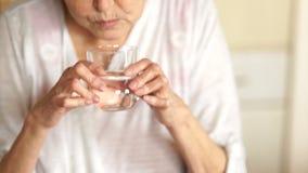 O aposentado lava para baixo uma tabuleta com água de um vidro Conceito da farmácia Mãos de uma mulher adulta no fundo de filme