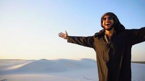 O Arabian companheiro feliz, caminhadas através do deserto, sorri e aprecia a vida na noite do verão n video estoque