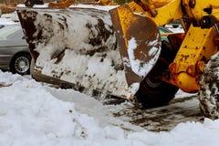 O arado de neve do trator cancela ruas da neve após o blizzard fotografia de stock