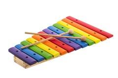 O arco-íris coloriu o xilofone de madeira do brinquedo contra o fundo branco fotos de stock royalty free