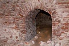 O arco de construção abandonado velho da parede de tijolo resistiu, aventura perigosa da catacumba abandonada da fortaleza Fotos de Stock Royalty Free
