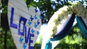 O arco do casamento decorado com pano, as flores e a palavra AMAM Ajustes do casamento video estoque