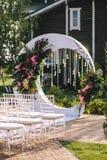 O arco do casamento no território do hotel sob a forma de um círculo branco decorado com flores, as ampolas e o cristal tran imagens de stock royalty free