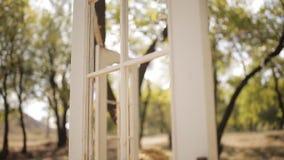O arco e as cadeiras brancos com coxins Arco do casamento no estilo rústico sob a forma das portas O sol brilha com vídeos de arquivo