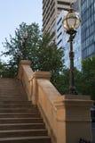 O arenito pisa com os postes de luz velhos da forma, construções modernas no fundo fotografia de stock royalty free