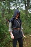 O arqueiro medieval com capa preta e as setas coloridas tremer está com curva Foto de Stock Royalty Free