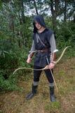 O arqueiro medieval com capa preta e as setas coloridas tremer está com seta Fotos de Stock