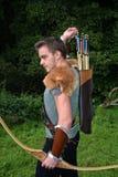 O arqueiro medieval novo com camisa chain alcança para a seta, com curva à disposição Fotos de Stock Royalty Free