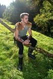 O arqueiro medieval novo com camisa chain senta-se no ramo na natureza na luz solar Fotografia de Stock