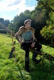 O arqueiro medieval novo com camisa chain senta-se no ramo na natureza na luz solar, chifre bebendo no st da mão, da seta e da cu Imagens de Stock Royalty Free