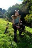 O arqueiro medieval novo com camisa chain senta-se no ramo na natureza na luz solar, chifre bebendo no st da mão, da seta e da cu Imagem de Stock Royalty Free