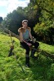 O arqueiro medieval novo com camisa chain senta-se no ramo na natureza na luz solar, chifre bebendo no st da mão, da seta e da cu Fotos de Stock Royalty Free