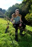 O arqueiro medieval novo com camisa chain senta-se no ramo na natureza na luz solar, chifre bebendo no st da mão, da seta e da cu Fotografia de Stock
