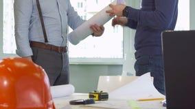 O arquiteto dá um rolo de planos da construção a seu colega fotos de stock royalty free