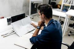 O arquiteto de cabelo escuro à moda novo nos vidros e em um casaco azul está trabalhando com documentos na mesa no escritório imagens de stock royalty free