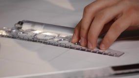 O arquiteto do homem tira um plano, gráfico, projeto, formas geométricas pelo lápis na grande folha de papel na mesa de escritóri filme