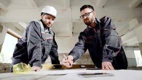 O arquiteto e o superintendente com um capacete para a proteção na cabeça estão discutindo a possibilidade de fatura filme